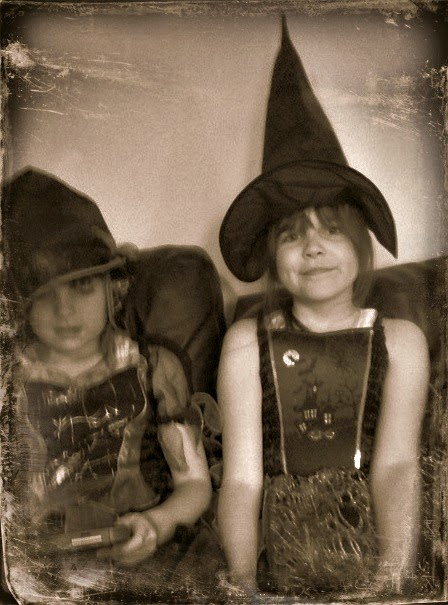 my two girls dressed up as witches when they were much younger, the photo has been turned to black and white and distressed.