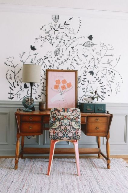 An old wooden desk with a a floral chair topped with a painting and a lamp and set against a handpainted mural on the wall