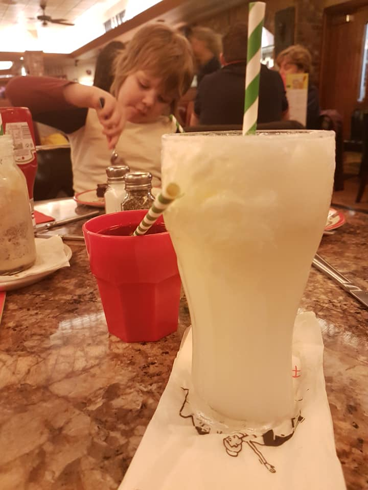 a soda float drink in the foreground with a little boy tucking into his dessert behind it