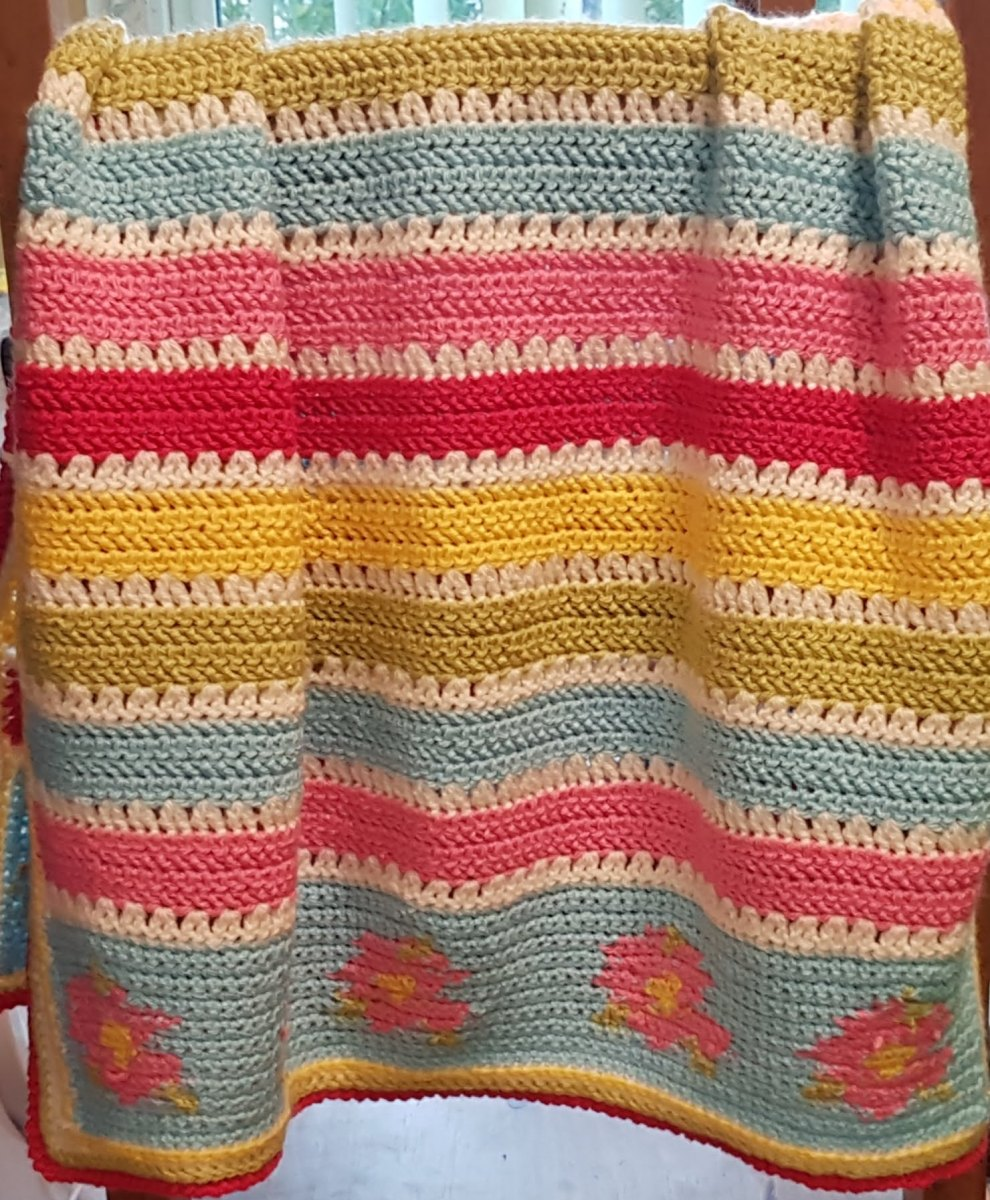 baby blanket crocheted in stripes of colourful wool.