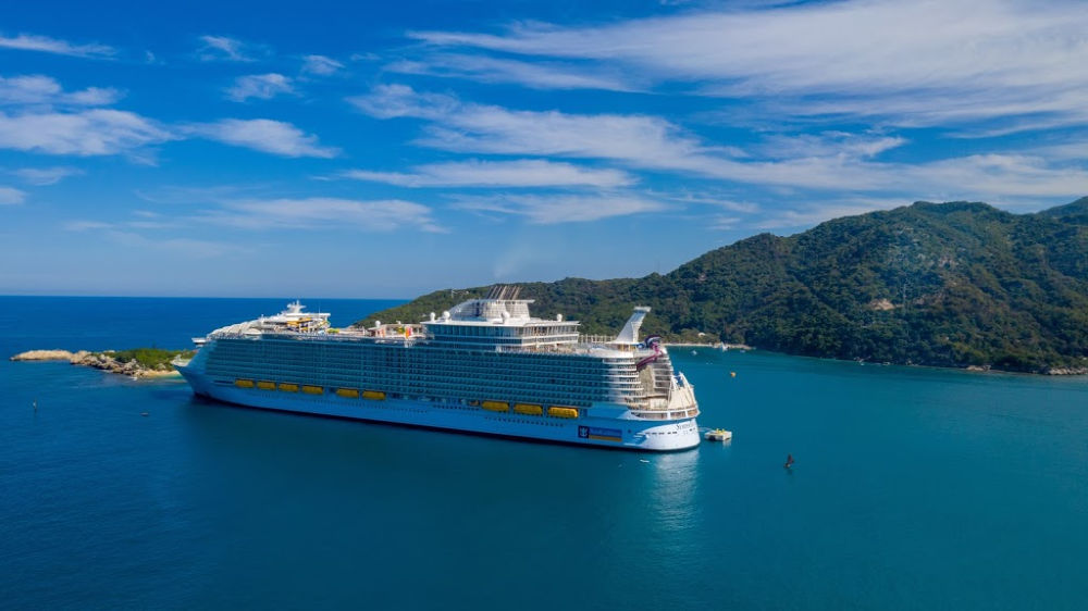 a very large cruise ship on the blue ocean with grassy hills in the background