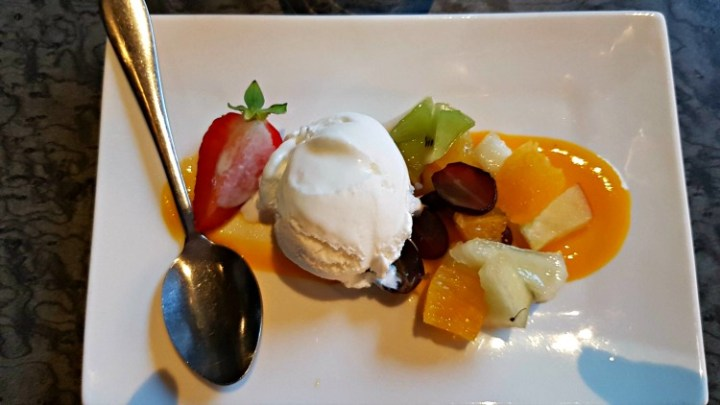 coconut ice cream with grapes, kiwi, mango, pear and strawberry with a mango sauce.