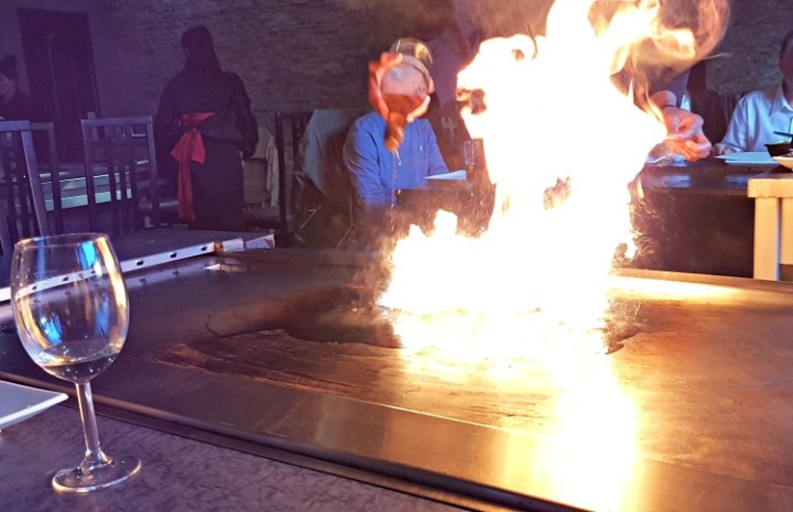 The flames on the griddle as the chef sets it alight