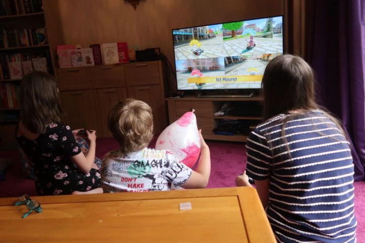 3 kids playing Mario Kart on the switch showing on tv.