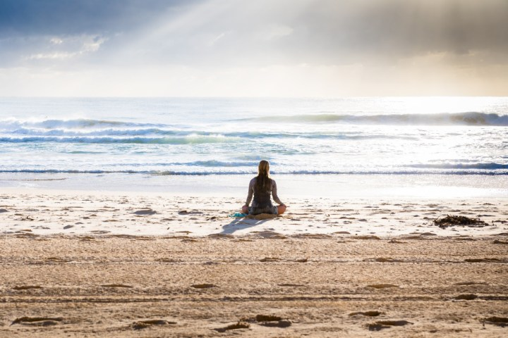 A woman sitting on an empty beach in a cross legged position looking out at the sea