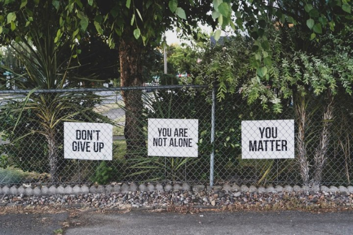 a fence with trees behind it and three signs saying, don't give up, you are not alone and You matter.