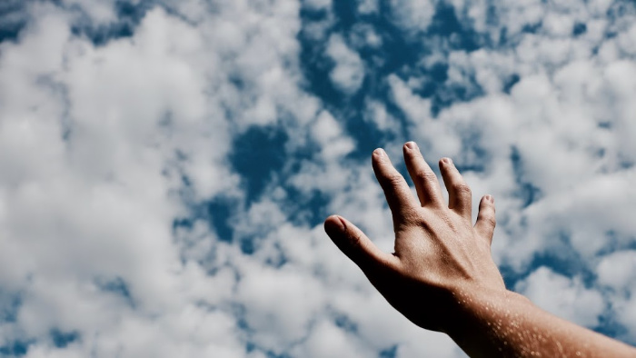 a hand reaching up to a cloudy sky