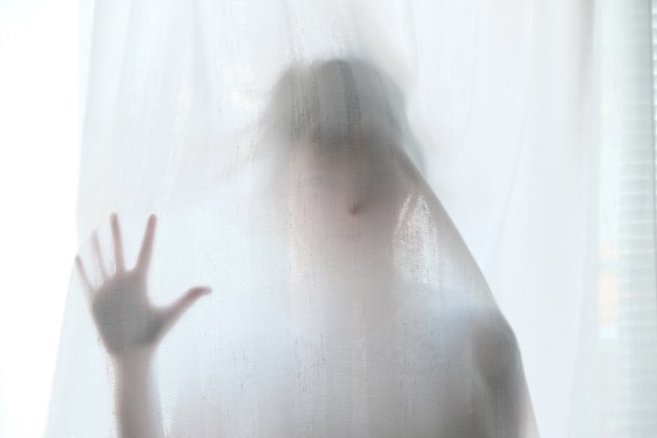 a person standing behind a voile curtain looking like  a ghost
