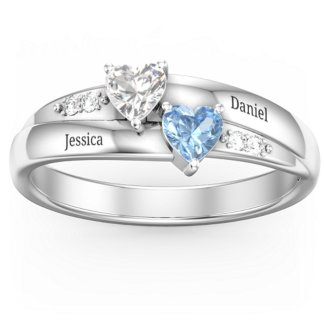two entwined silver rings wtih one blue and one white heart and two engraved names.