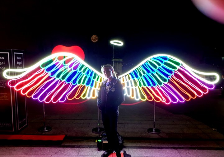 a young girl standing in front of Neon angel wings and halo