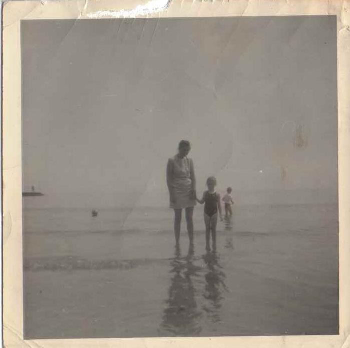 me and my Mum a long time ago, paddling in the sea. The photo is in black and and white.