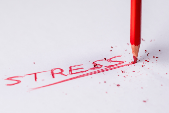 a white piece of paper with the word stress written on it in red pencil.