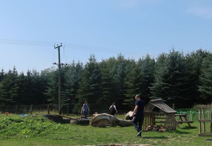 The wooden play area with the children and their Dad playing