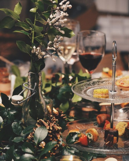 photo of party food and drink, a decorated bottle, a tiered plate of  cakes and nibbles and two glasses of wine, one white one red.