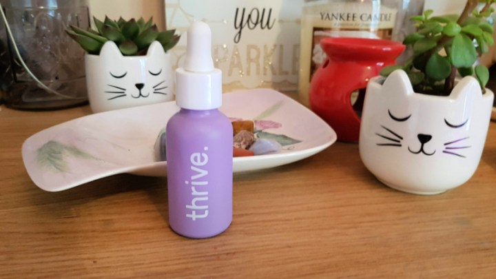 Photo showing a candle and oil burner in the background, a bowl full of crystals, two little plant pots with cacti and in front a bottle of Thrive CBD oil
