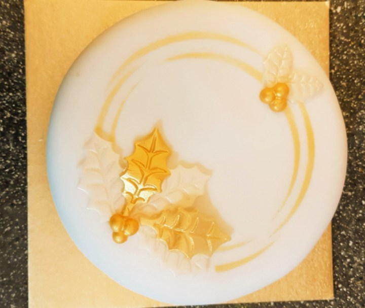 Christmas cake, white with gold decorations.