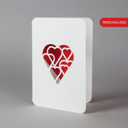 white hearts cut out on a red background card