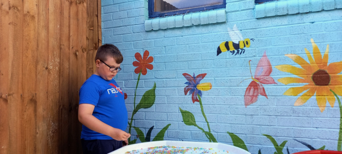The Little Man standing by a painted wall with flowers and bees