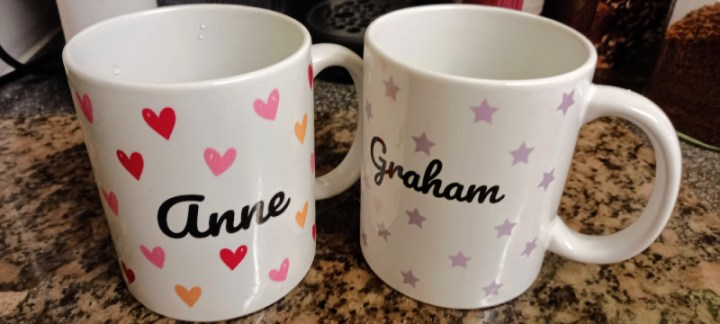 Two personalised mugs, one with hearts and the name Anne, the other with stars and the name Graham