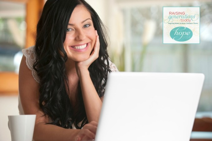 Happy woman looking at a laptop indoors, looking at camera