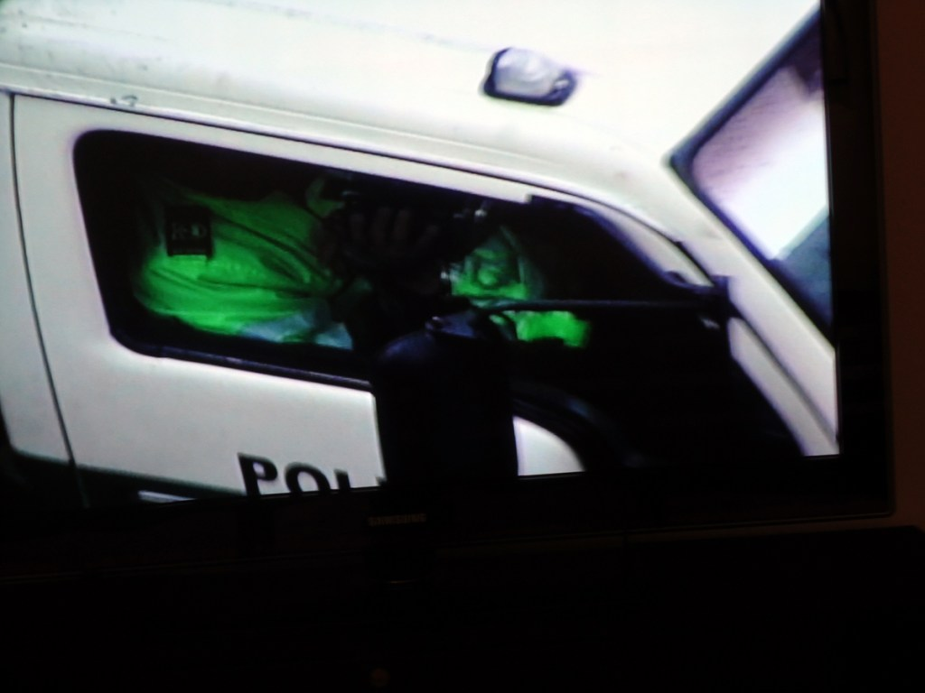 Image of a person in a police van filming someone.