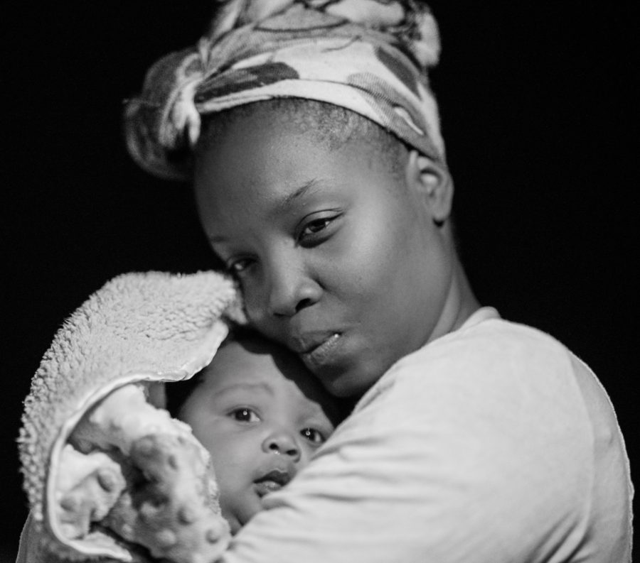 Greyscale photo of a Black woman holding a baby in a blanket