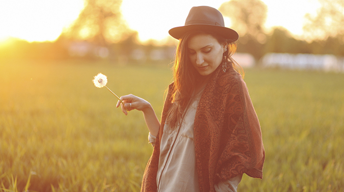 Girl wearing hat in a field holding a dandelion