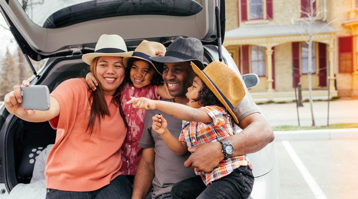 Family taking a selfie before a summer roadtrip