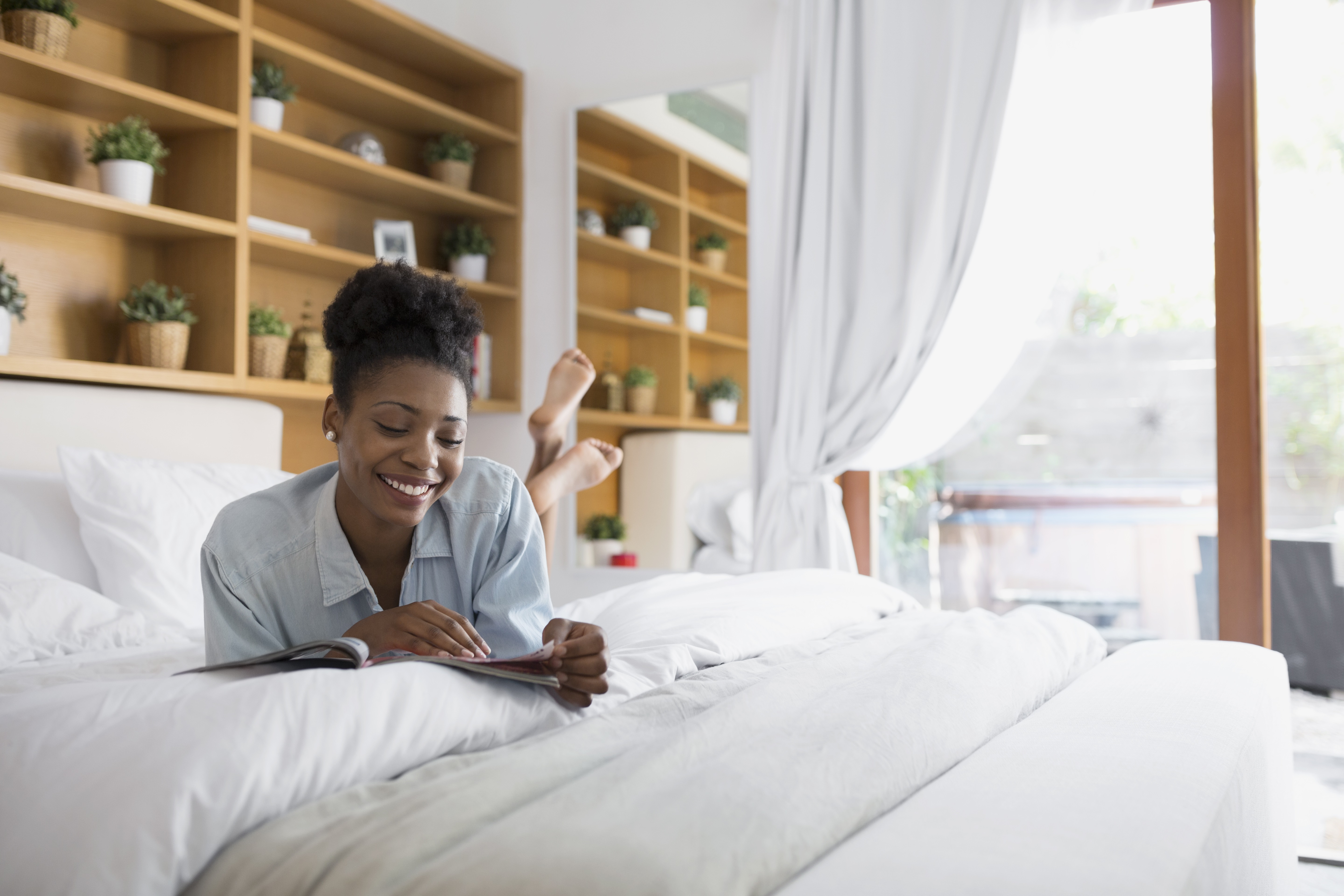 Woman reading in guest bedroom