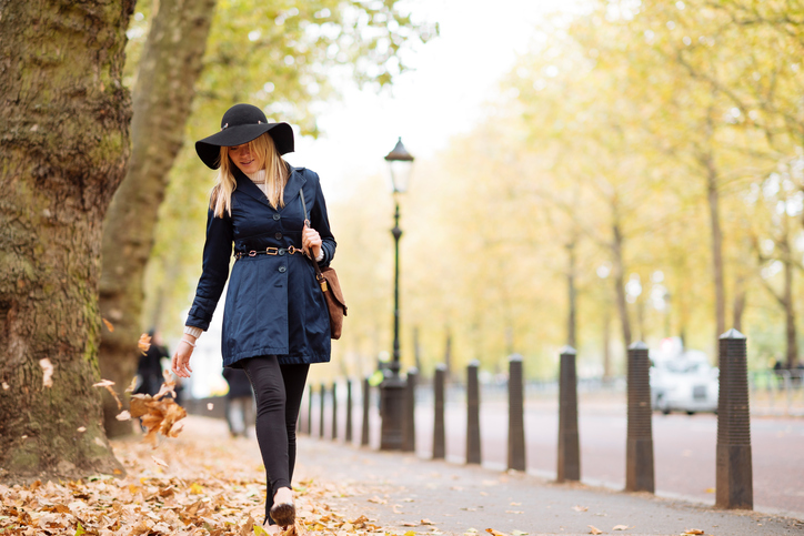 Stylish young woman strolling through autumn leaves in city park