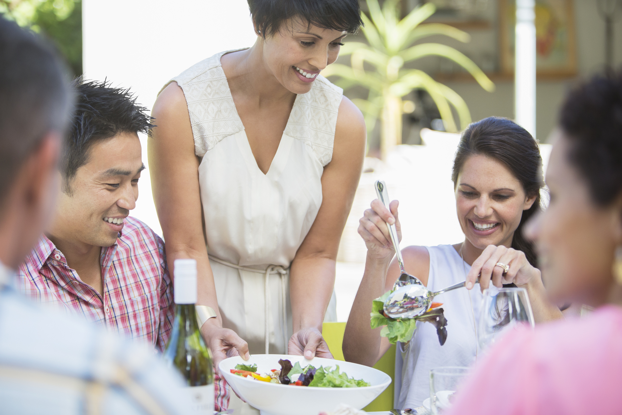 Woman serving friends at table outdoors