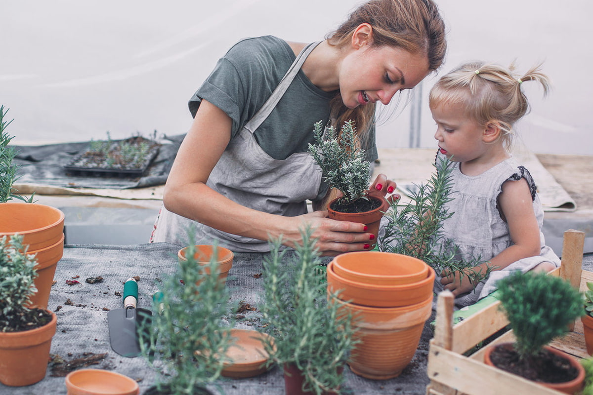 Woman and child potting plants