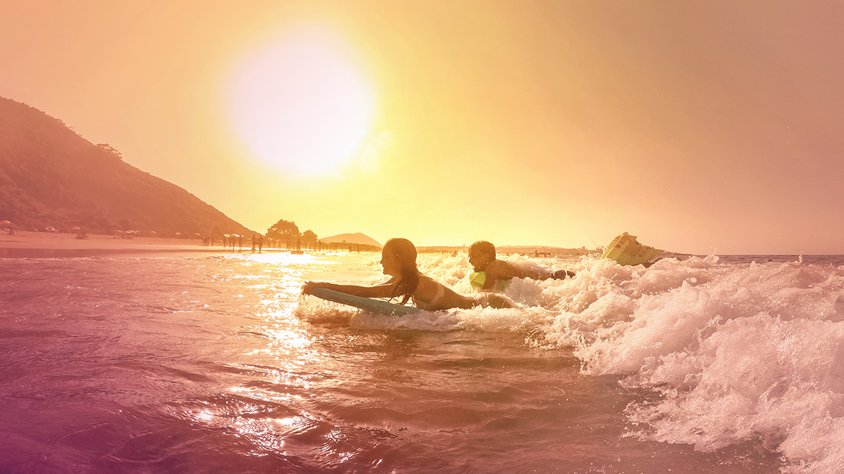 People surfing at sunset