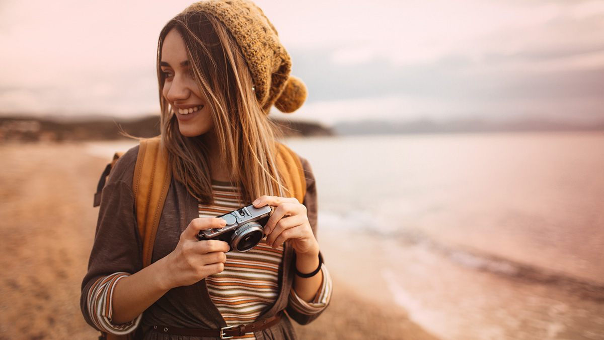 Girl on the beach holding a camera