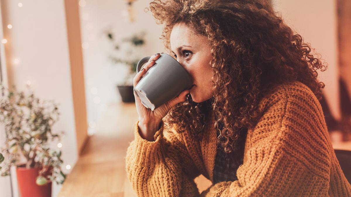 woman wearing a cardigan drinking from a mug