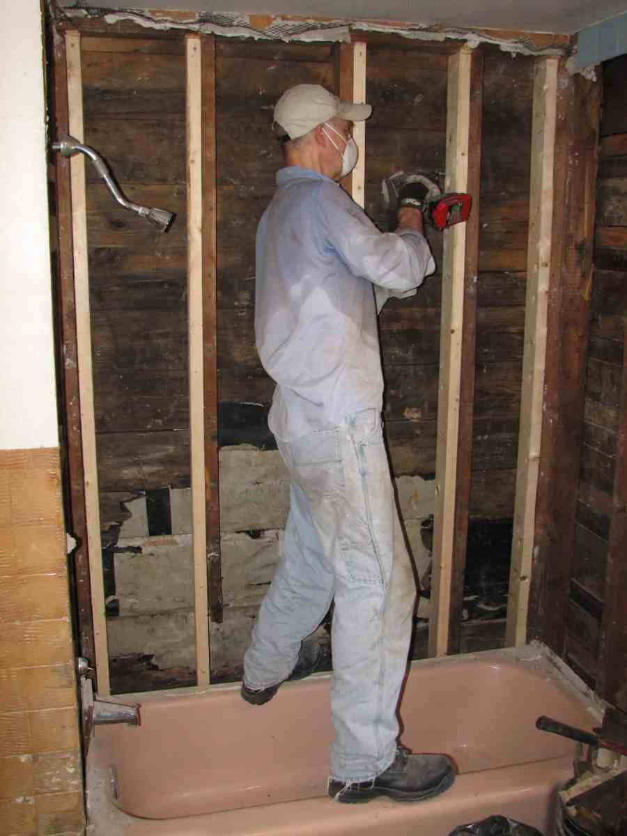 John repairing wall in an apartment bathroom as part of service with MCC SWAP in Elkhorn, WV.