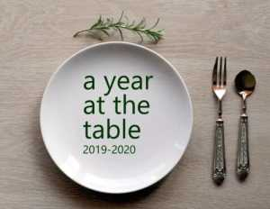 "A table place setting with ""A Year at the Table, 2019-2020"" written on the place."