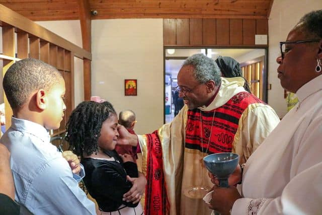 Priest blessing children during communion at St Ambrose Episcopal Church