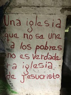 A sign in Spanish in front of a church.