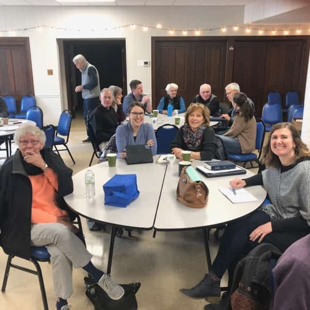 A group around the table with others in the background at the pop-up seminary on Feb. 15, 2020.