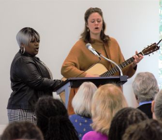 Ronda and Sus lead the congregation in a song, with Sus playing guitar.