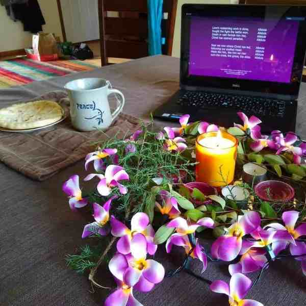 Communion elements, an Easter wreath with flowers and candles, and a laptop in the background.