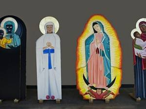 Four life-size cutout images different depictions of Mary in different attire.