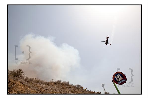 Un helicóptero contra incendios se dirige hacia una columna de humo