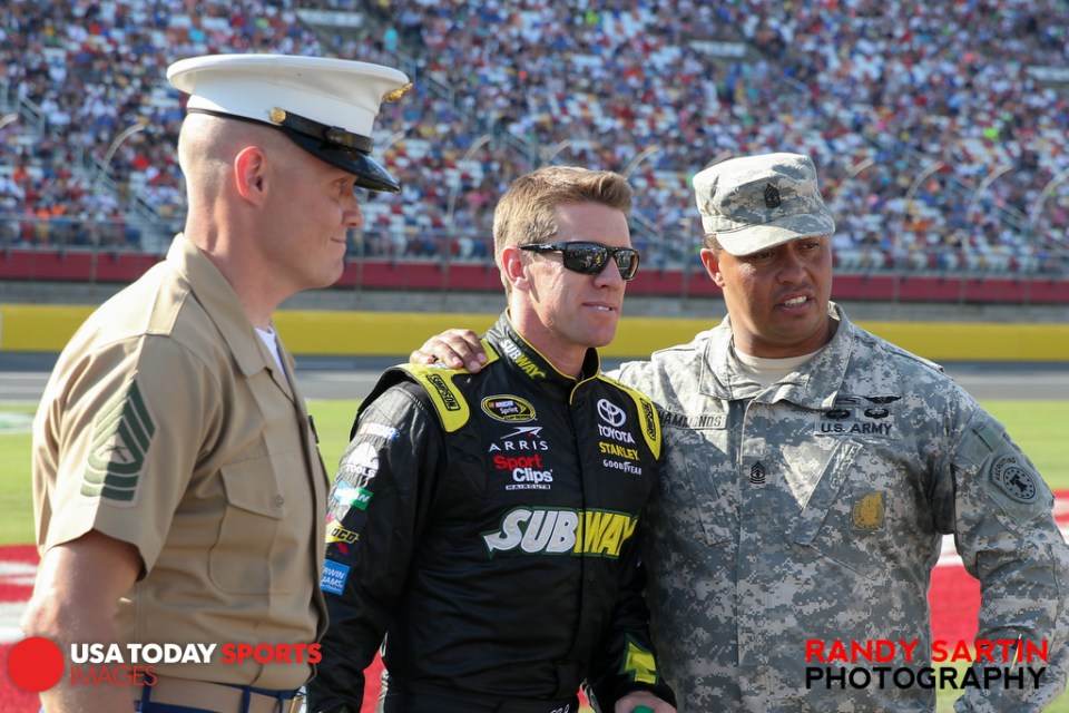 May 24, 2015; Concord, NC, USA; NASCAR Sprint Cup Series driver Carl Edwards (19) poses for a picture with members of the military before the Coca-Cola 600 at Charlotte Motor Speedway. Mandatory Credit: Randy Sartin-USA TODAY Sports