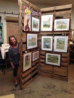Lynn Peterson peers around her stunning display of watercolors.