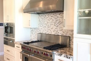 4 panel slider, bar faucets, glam light fixture, glam pendant light, glass mosaic tile wall, glass panel cabinet, kohler farm sink, large kitchen island, marble tile wall, painted stacked stone, subzero fridge, white kitchen faucet, white raised panel cabinet doors, Wolf appliances, wood plank porcelain tile, wrought iron room divider