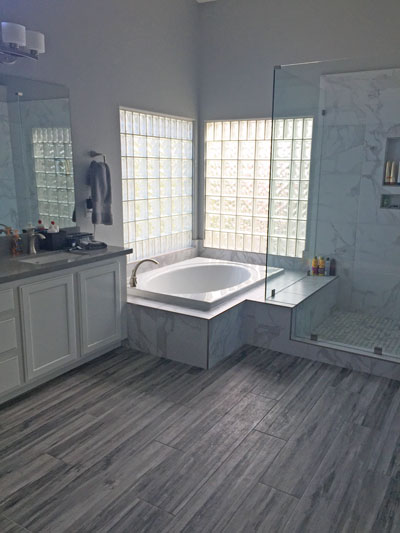 frameless glass shower enclosure, quartz countertops, wood plank look porcelain tile, marble look porcelain tile, brushed nickel faucet, brushed nickel hardware, mirror frame,double undermount sinks, shower niche,