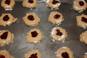 with your thumb make an indentation in the center of each cookie and fill with jelly