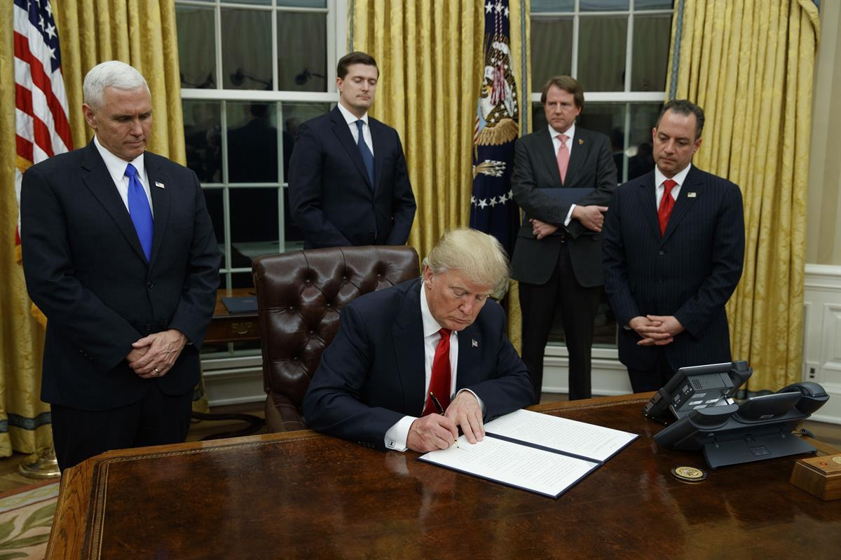 President Donald Trump, flanked by Vice President Mike Pence and Chief of Staff Reince Priebus, signs his first executive order on health care, Friday, Jan 20, 2017, in the Oval Office of the White House in Washington. (AP Photo/Evan Vucci)
